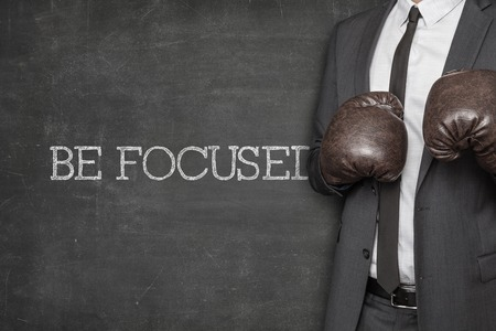 be alert: Be focused on blackboard with businessman wearing boxing gloves Stock Photo