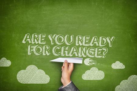 業務: 你準備好迎接變革的概念上的綠色黑板與商人手拿著紙飛機 版權商用圖片