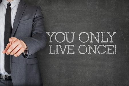 once person: You only live once on blackboard with businessman finger pointing