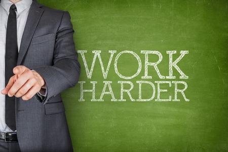 harder: Work harder on blackboard with businessman finger pointing Stock Photo