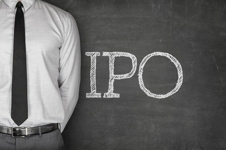 IPO or Initial public offering text on blackboard with businessman on side Standard-Bild