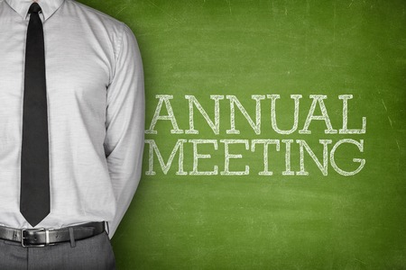job deadline: Annual meeting text on blackboard with businessman on side