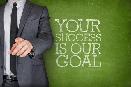 Your success is our goal on blackboard with businessman finger pointing Stock Photo