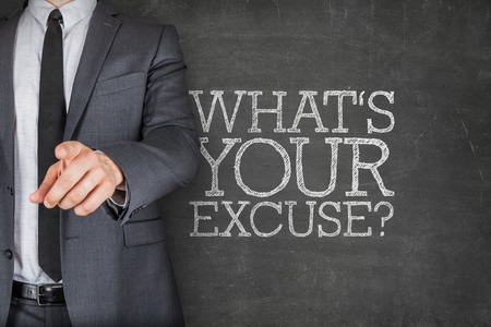 excuse: Whats your excuse on blackboard with businessman finger pointing