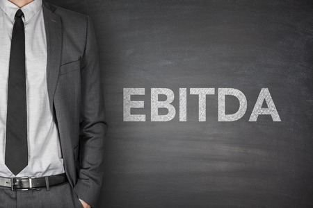 depreciation: Business acronym EBITDA Earnings before interest and taxes depreciation and amortization on black blackboard with businessman Stock Photo