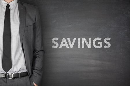 net income: Savings text on black blackboard with businessman
