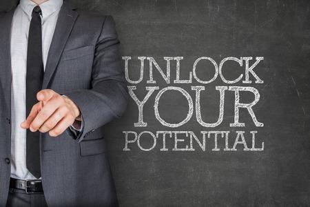 Unlock your potential on blackboard with businessman finger pointing Standard-Bild