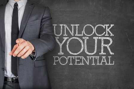 Unlock your potential on blackboard with businessman finger pointing Stock Photo
