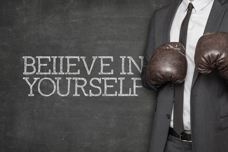 self assurance: Believe in yourself on blackboard with businessman wearing boxing gloves
