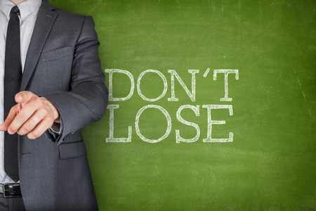 self assurance: Dont lose on blackboard with businessman finger pointing Stock Photo