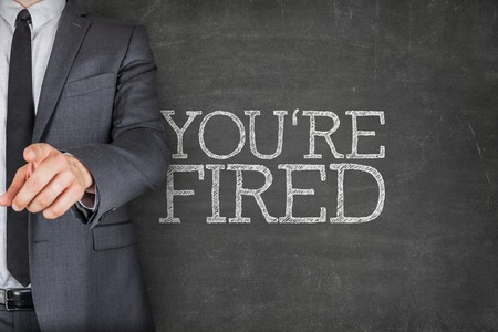 terminated: Youre fired on blackboard with businessman finger pointing