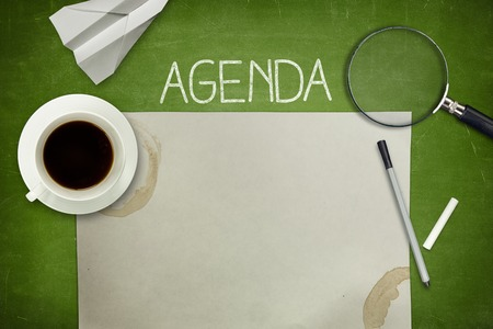 meeting agenda: Agenda concept on green blackboard with empty paper sheet and coffee cup Stock Photo
