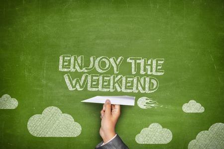 Disfrute el concepto de fin de semana en la pizarra verde con la celebración de la mano de negocios avión de papel