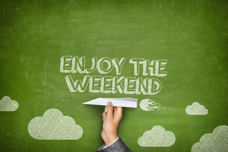 fin de semana: Disfrute el concepto de fin de semana en la pizarra verde con la celebración de la mano de negocios avión de papel