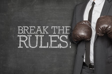 Break the rules on blackboard with businessman wearing boxing gloves
