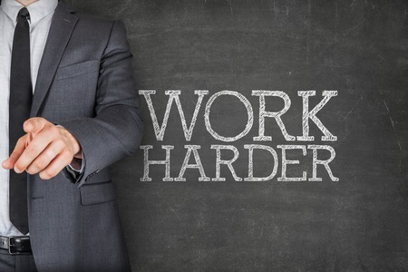 Work harder on blackboard with businessman finger pointing Stock Photo