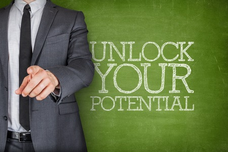 self discovery: Unlock your potential on blackboard with businessman finger pointing Stock Photo