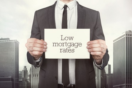 mortgage rates: Low mortgage rates on paper what businessman is holding on cityscape background