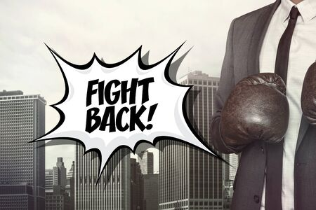 revolt: Fight back text with businessman wearing boxing gloves on cityscape background