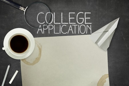 university word: College application concept on black blackboard with empty paper sheet and coffee cup
