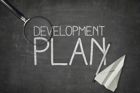 plan: Development plan concept on black blackboard with empty paper sheet and coffee cup Stock Photo