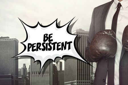 constant: Be persistent text with businessman wearing boxing gloves on cityscape background Stock Photo