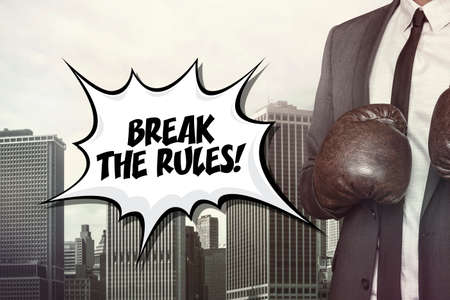 rebellious: Break the rules text with businessman wearing boxing gloves on cityscape background Stock Photo