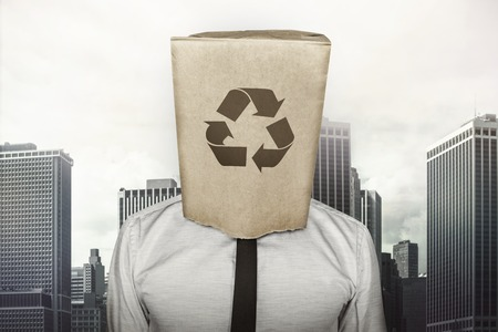 inventiveness: Recycling icon on paper bag what businessman is wearing on head on cityscape background