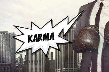 karma concept: Karma text with businessman wearing boxing gloves on cityscape background