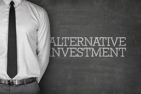 investments: Alternative investment text on blackboard with businessman on side Stock Photo