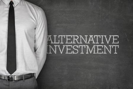 Alternative investment text on blackboard with businessman on side Foto de archivo