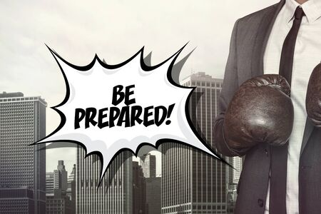 prepared: Be prepared text with businessman wearing boxing gloves on cityscape background Stock Photo