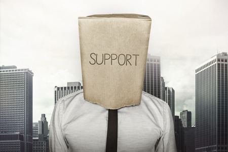 head support: Support text on brown paper bag which businessman has on head on cityscape background