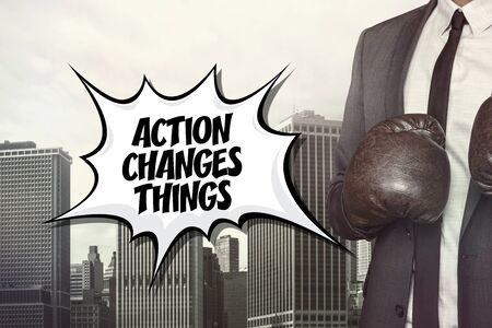 alter: Action changes things text with businessman wearing boxing gloves on cityscape background Stock Photo