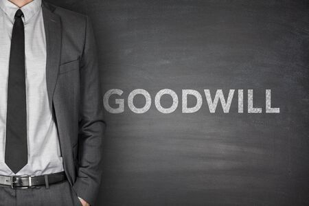 goodwill: Goodwill text on black blackboard with businessman