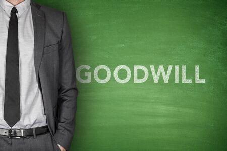 goodwill: Goodwill text on green blackboard with businessman Stock Photo