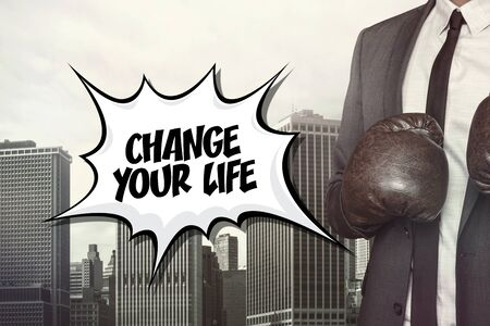 life change: Change your life text with businessman wearing boxing gloves on cityscape background Stock Photo