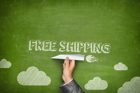 Free shipping concept on green blackboard with businessman hand holding paper plane