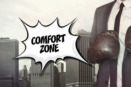 liberation: Comfort zone text with businessman wearing boxing gloves on cityscape background