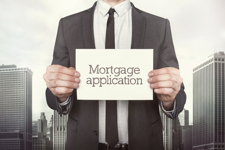 mortage: Mortgage application on paper what businessman is holding on cityscape background Stock Photo