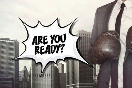 forewarning: Are you ready text with businessman wearing boxing gloves on cityscape background Stock Photo