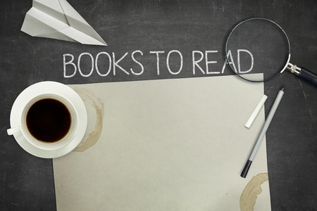 reading material: Books to read concept on black blackboard with empty paper sheet and coffee cup