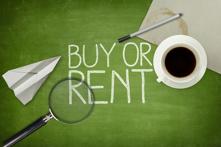 buying questions: Buy or rent concept on green blackboard with empty paper sheet and coffee cup