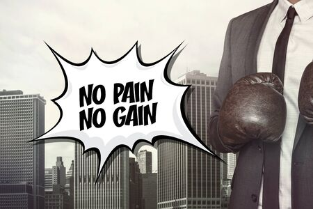 gain: No pain no gain text with businessman wearing boxing gloves on cityscape background Stock Photo