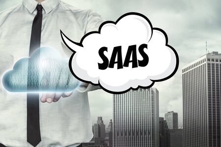 saas: Saas text on cloud computing theme with businessman on cityscape background Stock Photo
