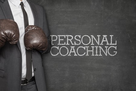 Personal coaching on blackboard with businessman wearing boxing gloves Banco de Imagens - 43091330