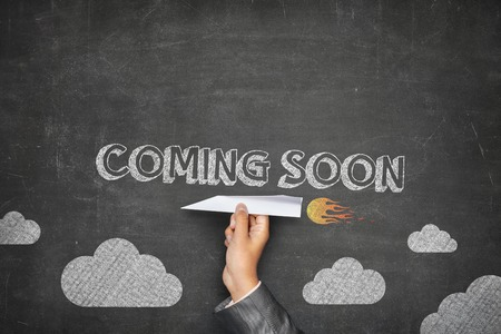 presently: Coming soon concept on black blackboard with businessman hand holding paper plane