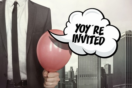 Youre invited text on speech bubble with businessman holding balloon on cityscape background Stock Photo