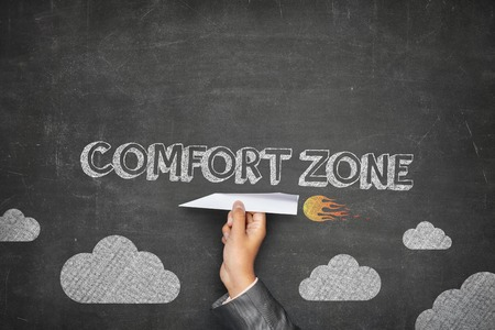safety slogan: Comfort zone concept on black blackboard with businessman hand holding paper plane