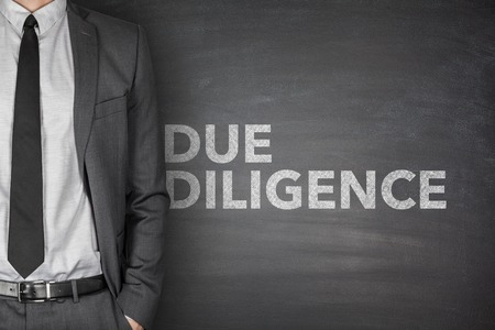 acquisitions: Due diligence on black blackboard with businessman
